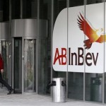 A man walks past a logo at the headquarters of Anheuser-Busch InBev